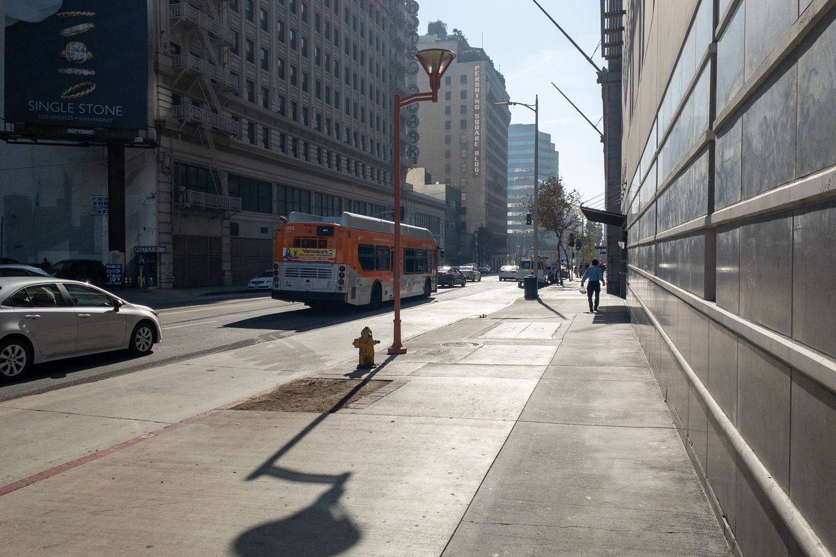 A bus and a car move past a nearly empty sidewalk