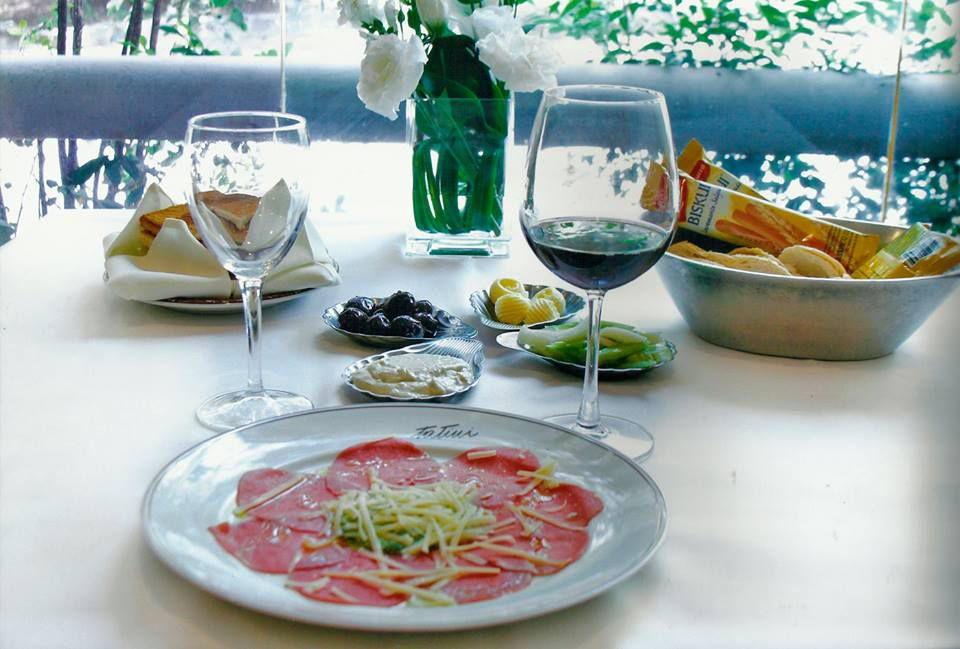 Thinly shaved meat is arranged on a plate in front of two glasses of wine, several other small plate and bread baskets, and a vase of flowers, all on a bright outdoor patio.