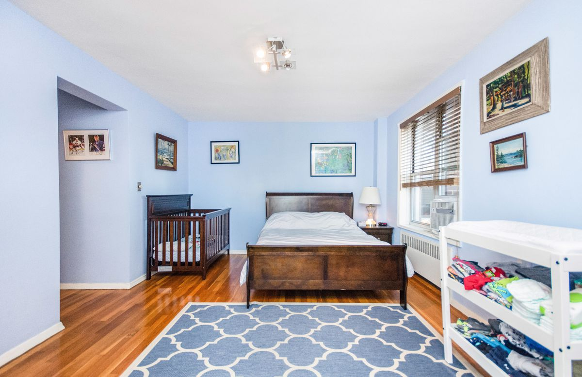 A bedroom with light blue walls, a rug, a crib, and a medium-sized bed.