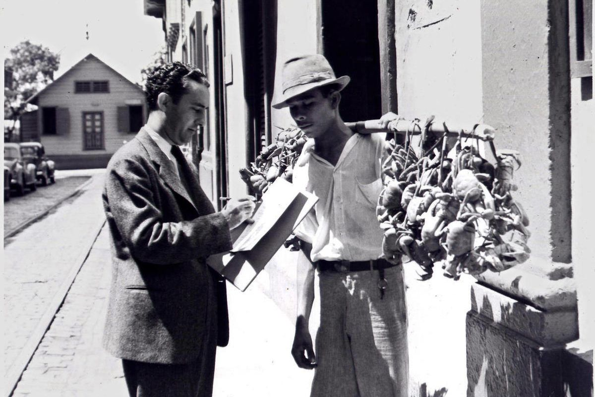 In this 1940 photo provided by the U.S. Census Bureau, an enumerator collects data from a street vendor carrying a poll of fresh crabs in Puerto Rico. Technical issues plagued the 1940 Census website on Monday, April 2, 2012, the first day that it became