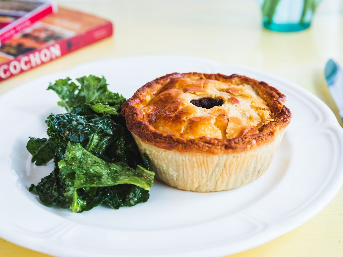 A small meat pie on a white plate beside a small salad