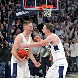 Aggie teammates Sam Merrill, left, and Justin Bean embrace at the end of Utah State's 81-76 upset of No. 12 Nevada on March 2, 2019, at the Spectrum.