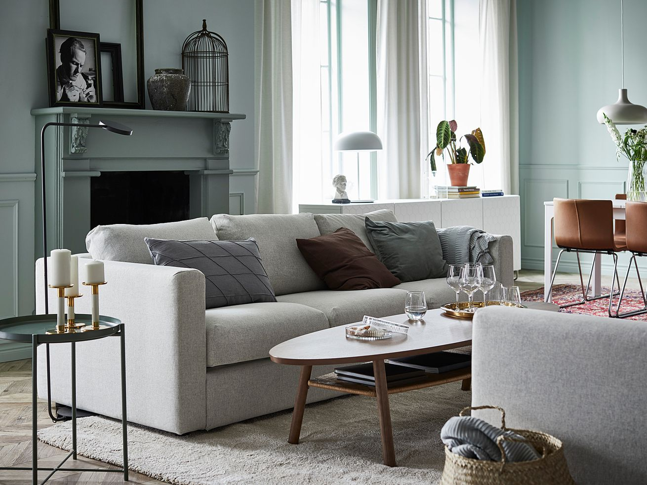 A living room features a white couch with throw pillows, light teal walls, a coffee table, and breezy white curtains.
