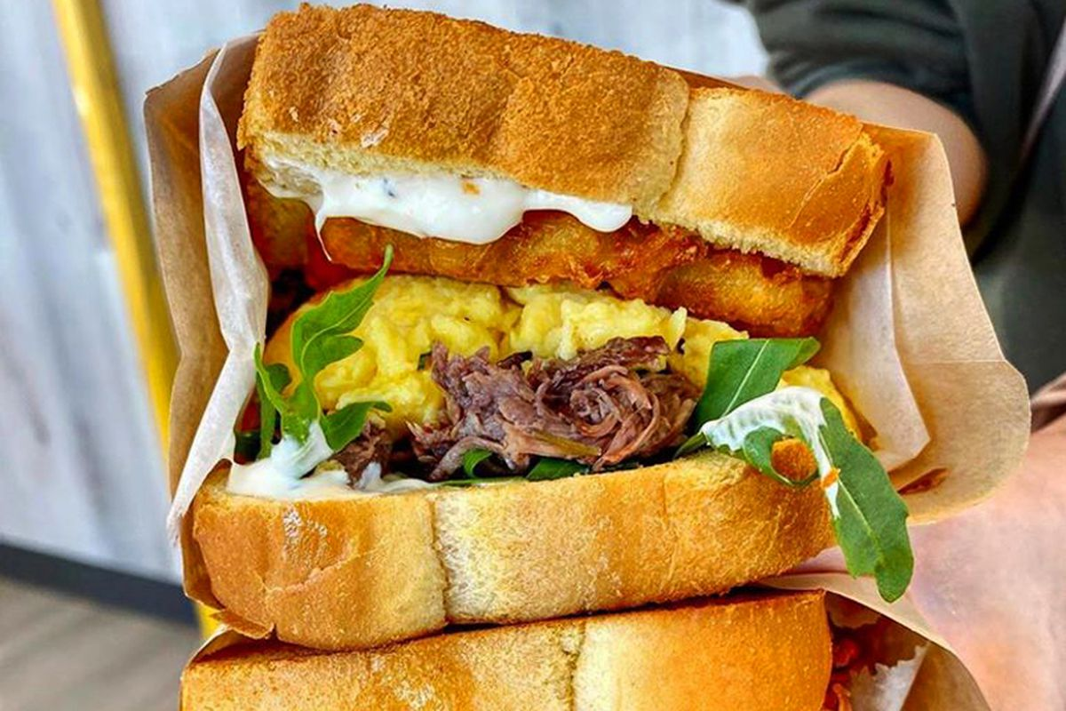 """The Egg Sammie""""stack"""" filled with meat, potatoes and buttermilk fried chicken, available for curbside take out."""