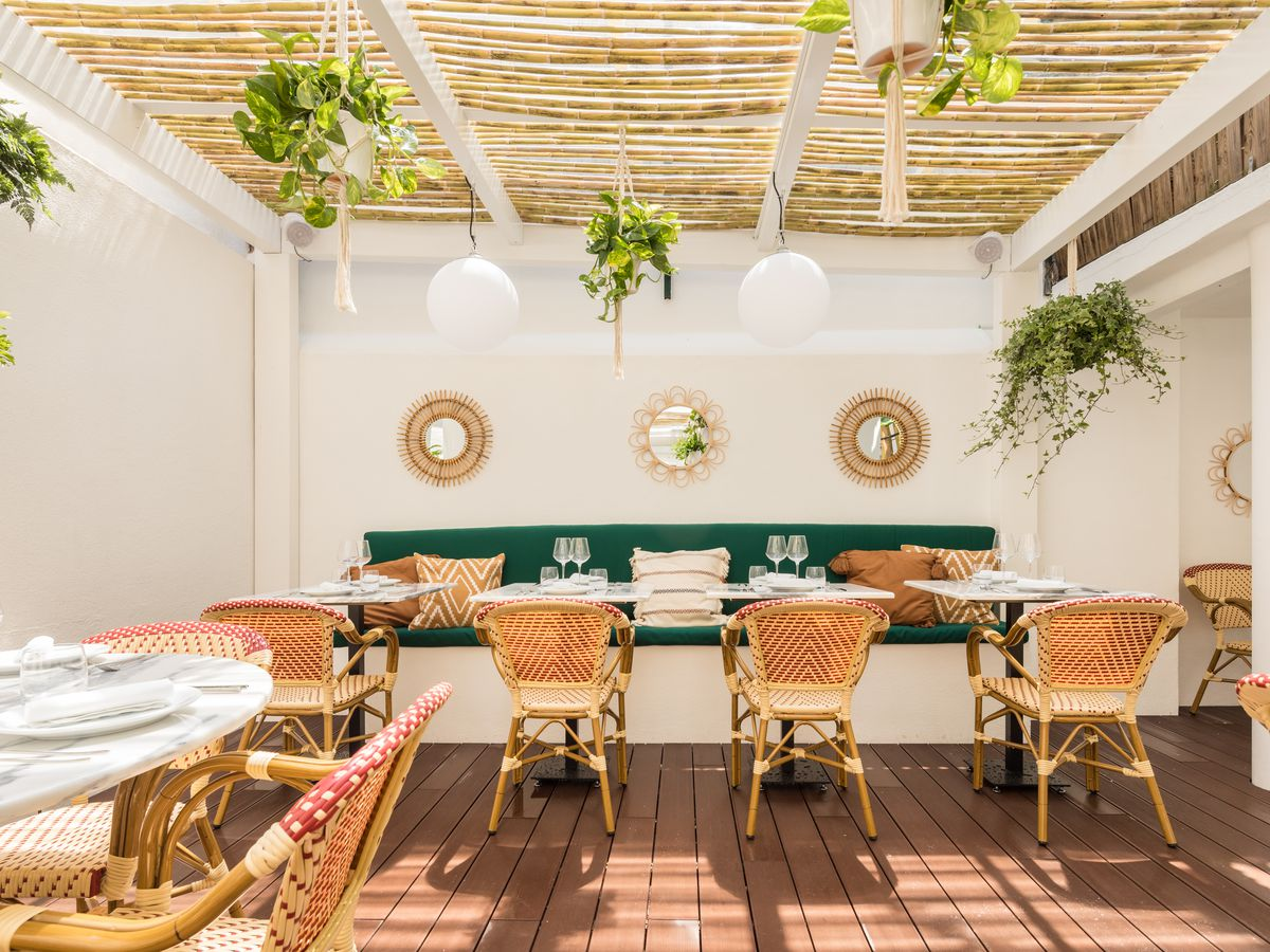 A covered patio, with wicker chairs, set tables, hanging plants