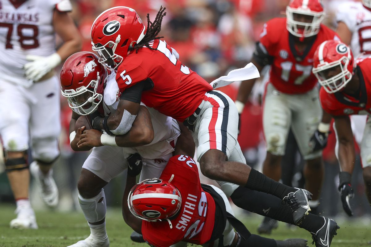 KJ Jefferson of the Arkansas Razorbacks is tackled by Christopher Smith and Kelee Ringo of the Georgia Bulldogs in the first half at Sanford Stadium on October 2, 2021 in Athens, Georgia.