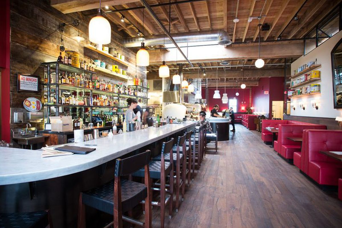 The bar at Trifecta Tavern, which faces a line of red booths under a wood ceiling