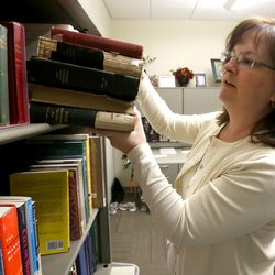Lisa Tait, research historian, pulls out a stack of The Young Woman's Journals in her office at the LDS Church History Library in Salt Lake City on Thursday, Dec. 3, 2015.