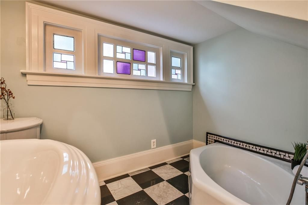 A small bathroom with a white tub and some stained glass windows.