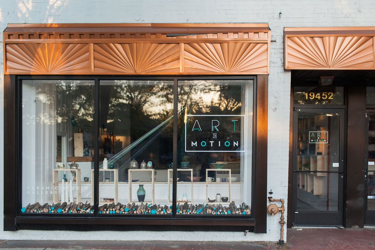 """A storefront with bronze awning and """"Art in Motion"""" in neon letters"""