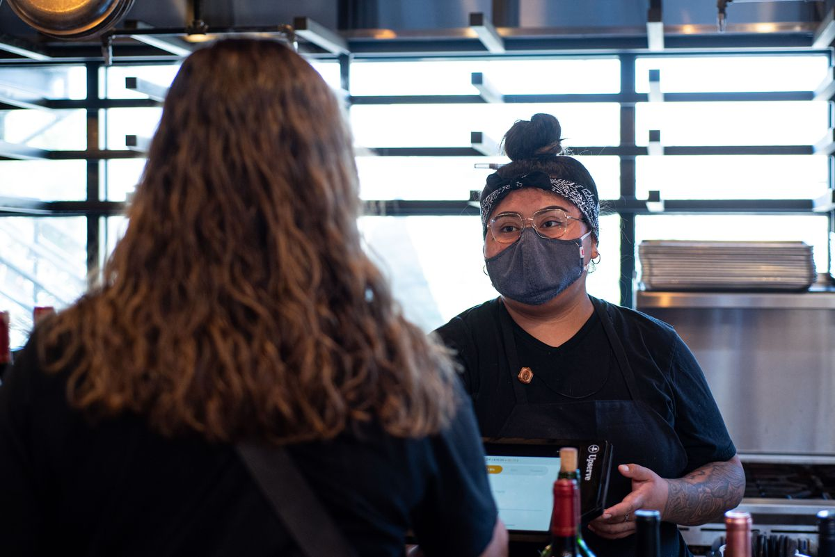An employee with glasses and a mask on takes an order at a kiosk.