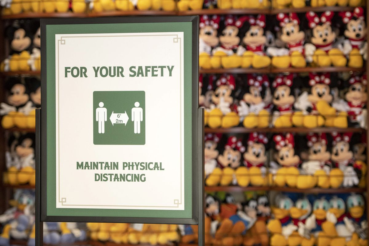 a social distancing sign in front of plush minnie mouse toys.