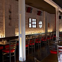 Spirit candles line the exposed brick wall