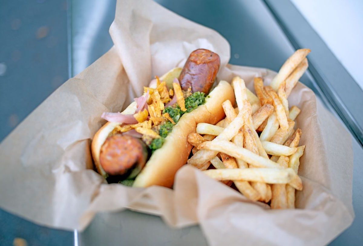 A sausage in a bun, topped with onions and chimichurri, stuffed in a paper-lined basket alongside a pile of fries
