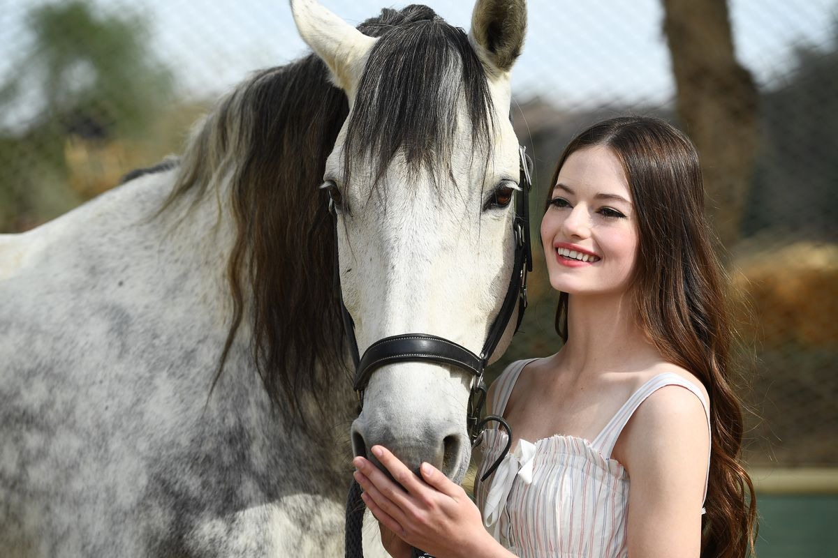 Mackenzie Foy smiling and cradling the nose of a dapple-grey Lusitano horse.