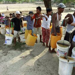 In this photo taken on Saturday, April 21, 2012, local residents carry plastic containers on their shoulders as they line up to fetch drinking water from a lake in Yangon, Myanmar.  Earth Day will be marked on April 22.