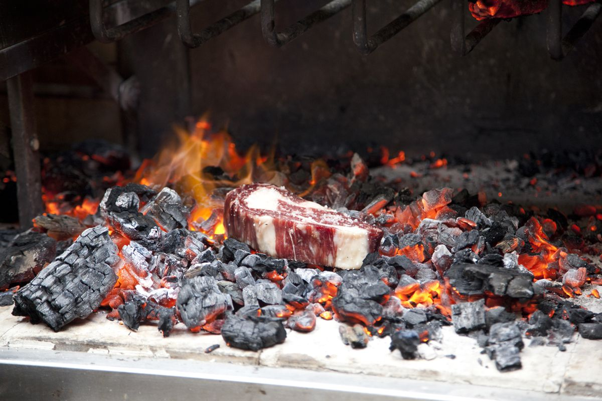 A thick hunk of marbled meat grills directly on a coal fire