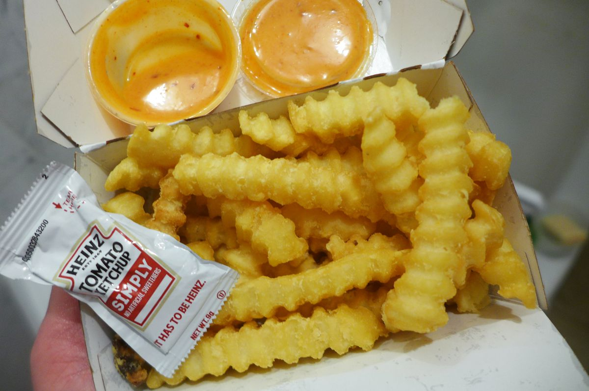 Ripple cut fries in a white cardboard box with orange sauce and a packet of ketchup.