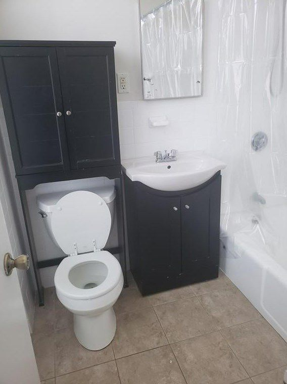 A bathroom with a cabinet above the toilet, which is next to the sink which is next to the shower.