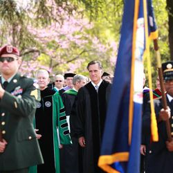 Walking behind an ROTC color guard, Mitt Romney walks with administrators and faculty of Southern Virginia University prior to commencement exercises on April 27, 2013.