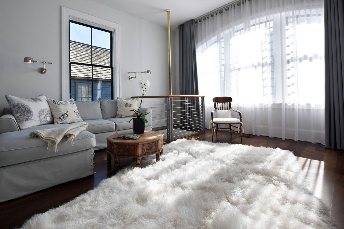 A living room has a white fluffy rug, gray couch, sheer window dressings, and a brass fireman's pole in the corner.