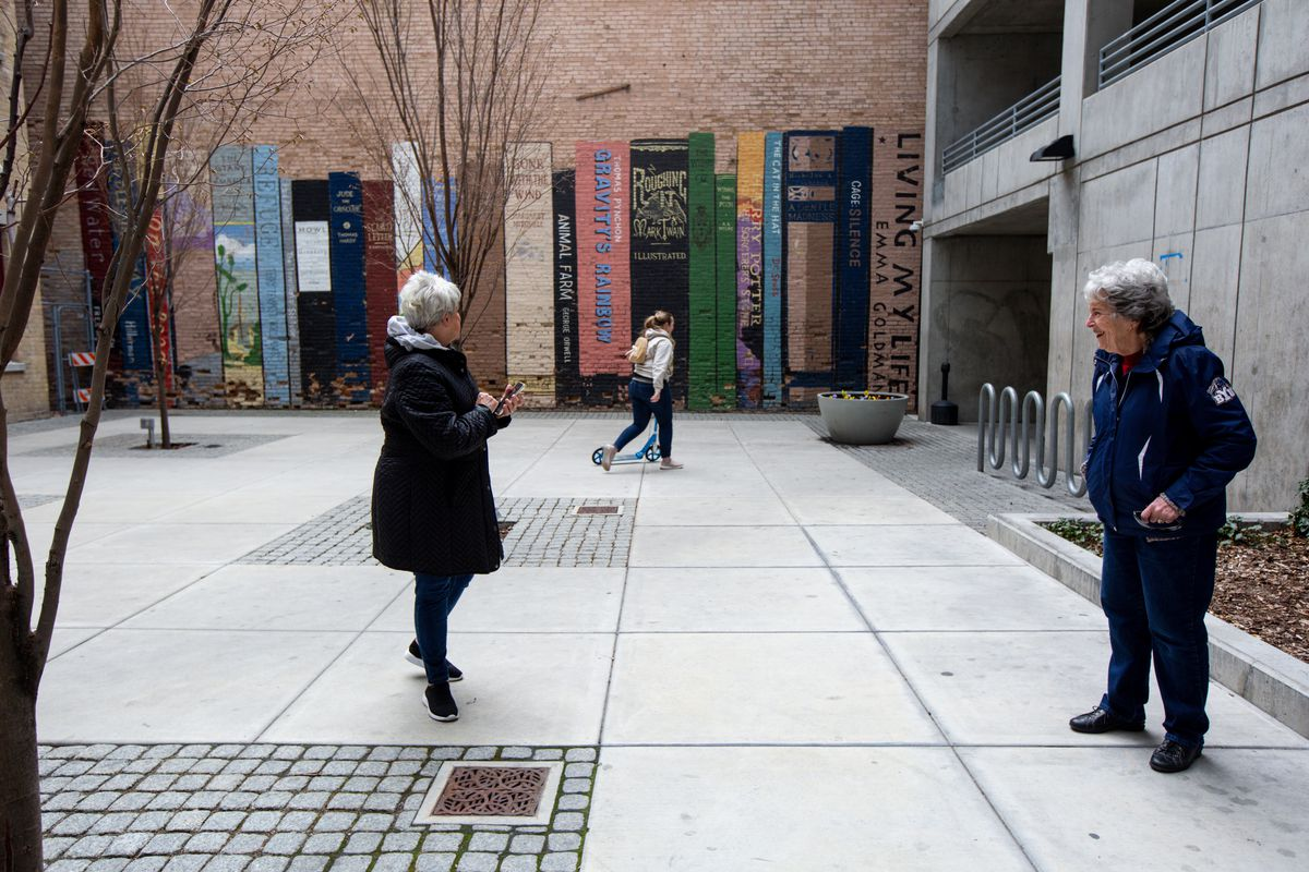 Neighbors Louise Jones, left, and Cheryl Doty,right, look for art while practicing social distancing during a walk of the nearly empty streets of downtown Salt Lake City on Friday, March 27, 2020.