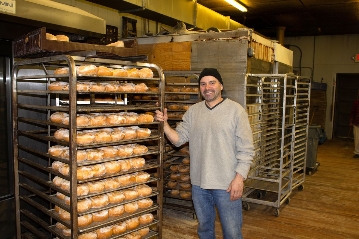 A baker wearing a black beanie stands in front of a speed rack stacked with loaves of bread, which are cooling