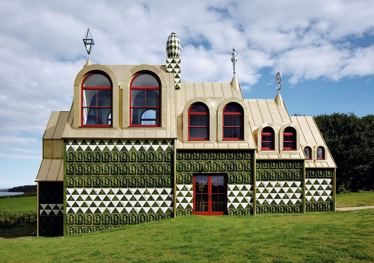 A house cladded in green and white ceramic tile with red windows and doors, a gold roof, and black and white decorative finials placed on top of the roof