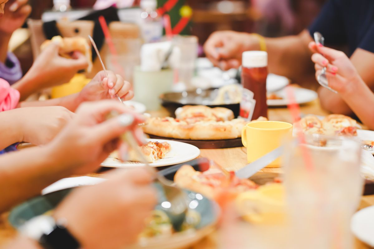 Hands crowded over a long dining room table, covered in plates of pizza, pasta, burgers, and fries.