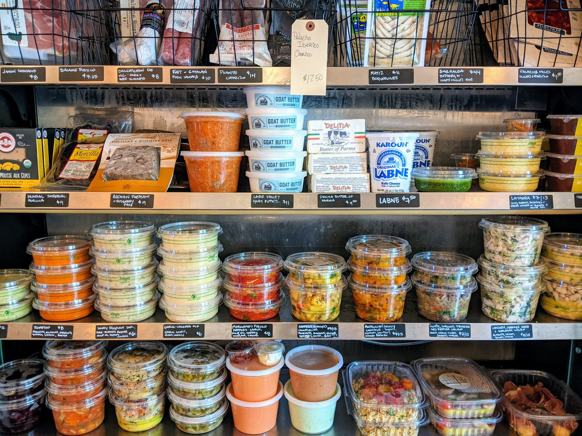 Plastic containers of labneh, meats, and dips fill out rows of shelves at Nido.