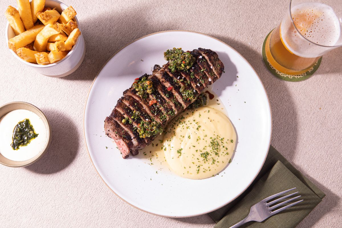 White plate with steak and pureed potatoes with fries and a beer in cups on the table