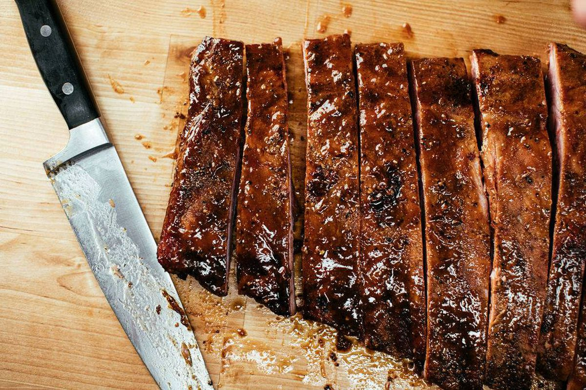 a rack of ribs, sliced and covered in barbecue sauce, sitting on a cutting board next to a knife