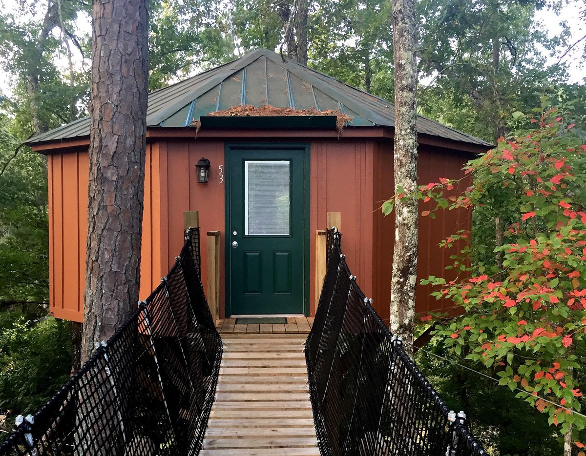 A circular copper-colored building with green door surrounded by trees and wooden ramp leading to the door.