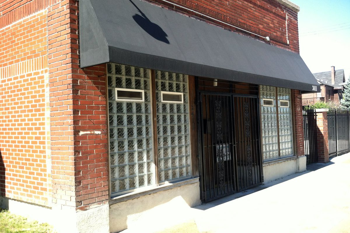 """The Le Petit Dejeneur building is gated and displays a """"For Sale"""" sign."""