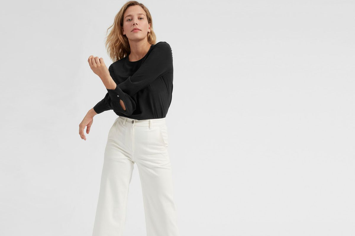 A model in a black shirt and white pants from Everlane.