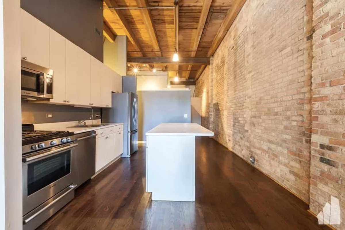 An open kitchen with an island, white cabinets, a timber ceiling, and a brick accent wall.