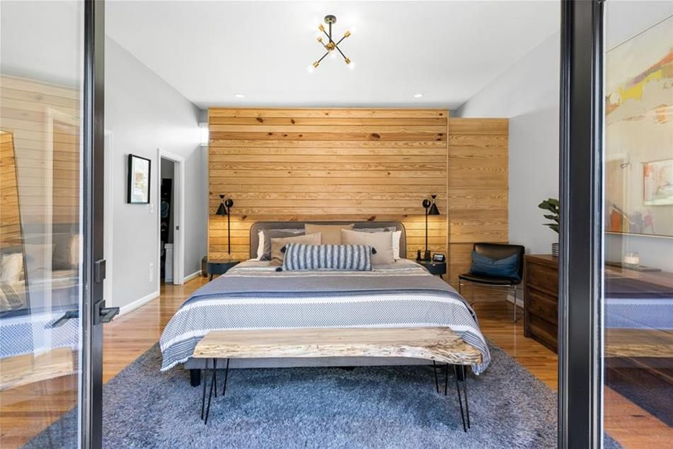 A large bedroom with a wooden wall.