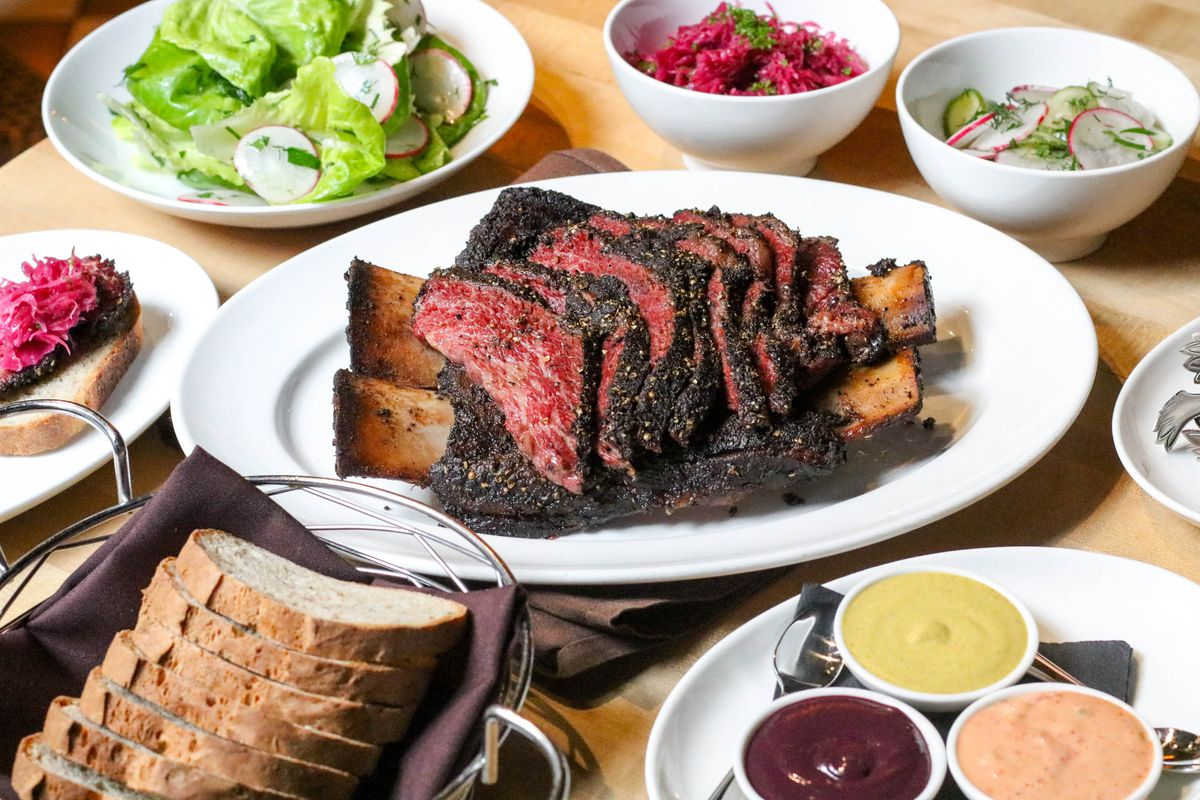 A platter of smoked short ribs in the center of several vegetables dishes