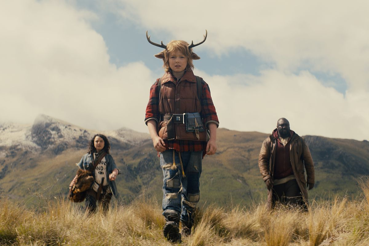 Deer boy Gus (Christian Convery) walks ahead of his adult allies in front of the mountains in season 1 of Netflix's Sweet Tooth.