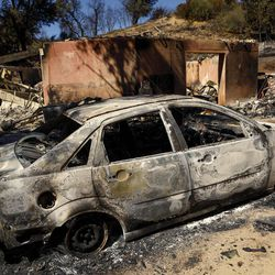 A burned out car sits next to a destroyed home after a wildfire in Santa Margarita, Calif., Wednesday, June 28, 2017.