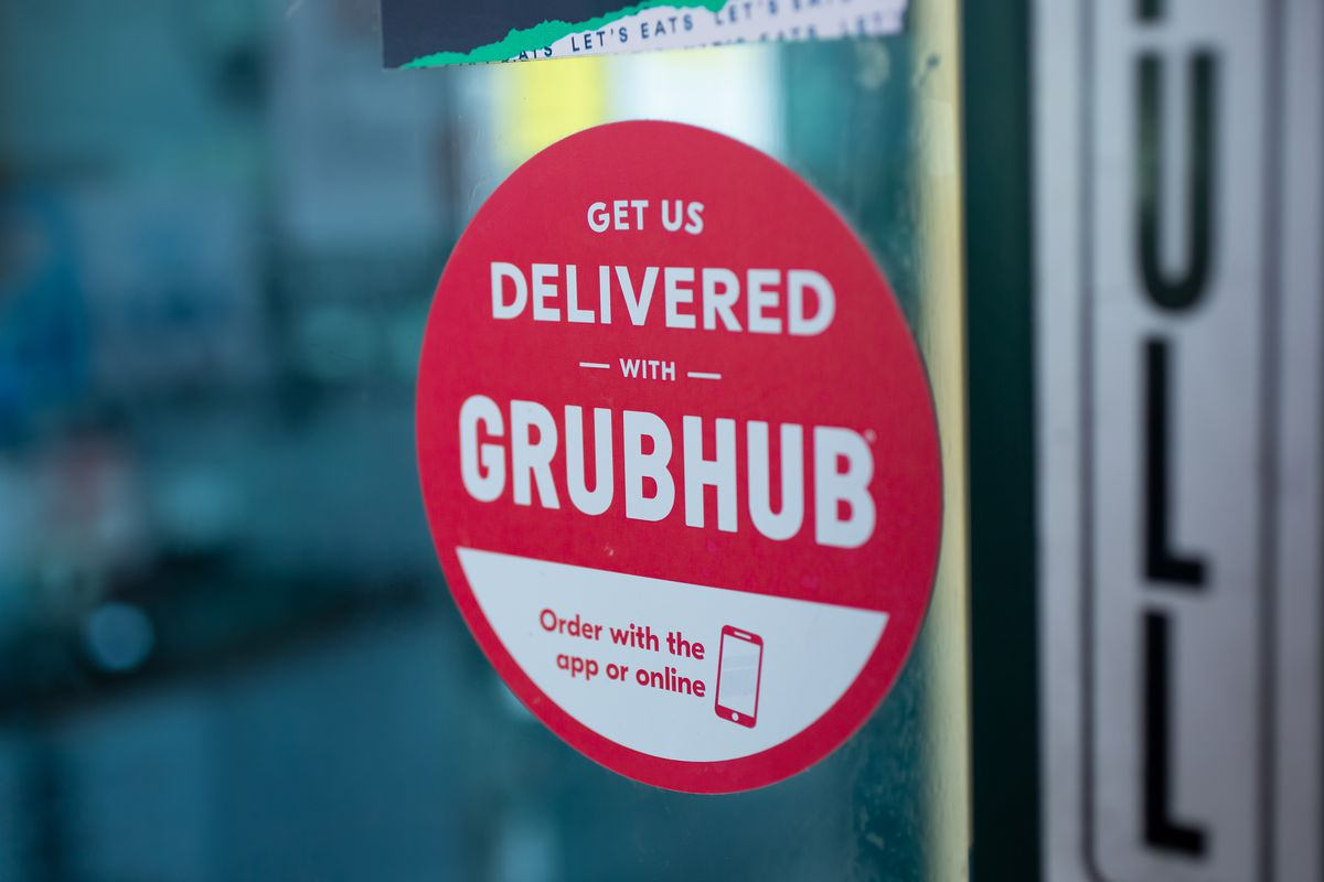 """""""Delivered with Grubhub"""" red sticker on a restaurant door."""