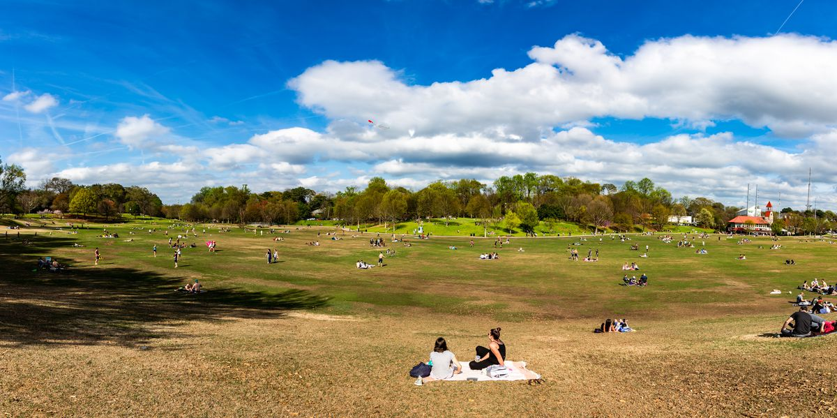 Groups of people picnics on the meadow at Piedmont Park in Midtown Atlanta COVID-19