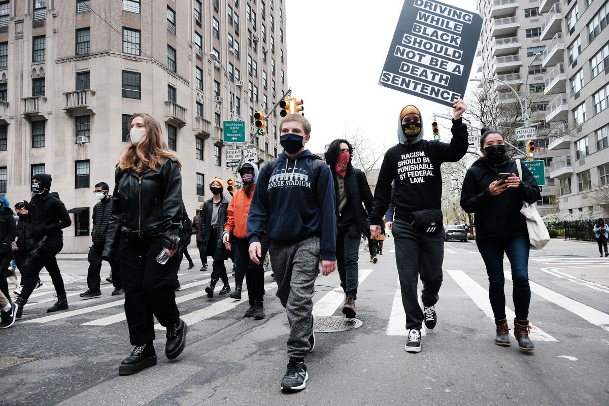 "A loose tangle of people, largely in black, march through the middle of a street, surrounded by skyscrapers. One holds a large black and white sign reading, ""Driving while Black should not be a death sentence."""