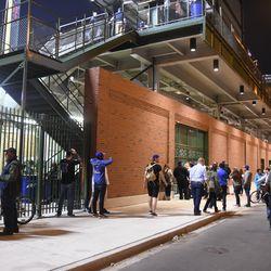 "8:47 p.m. Fans gathered outside of Gate Q (the ""knothole"" gate) on Waveland -"