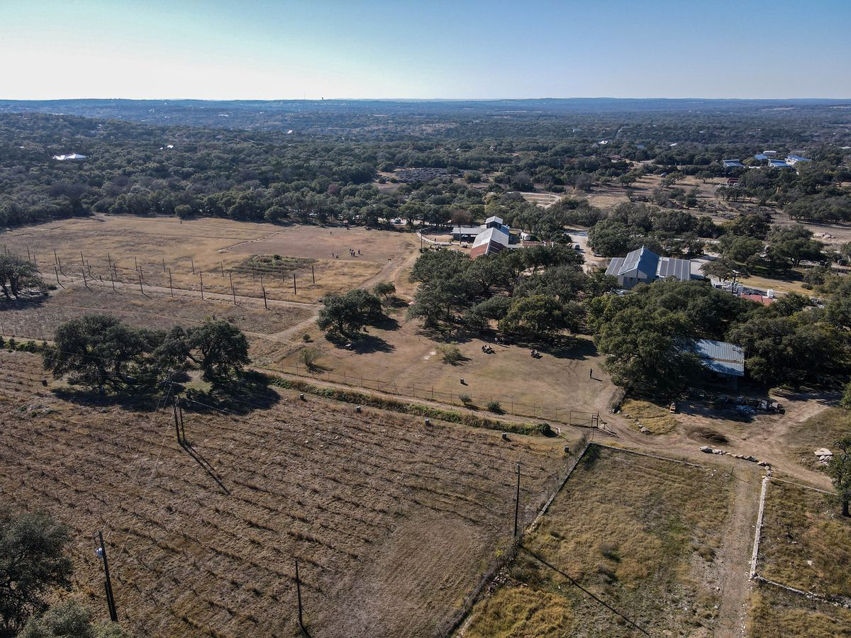 An aerial view of farm and vineyard land with a section of lined crops, plus trees and houses