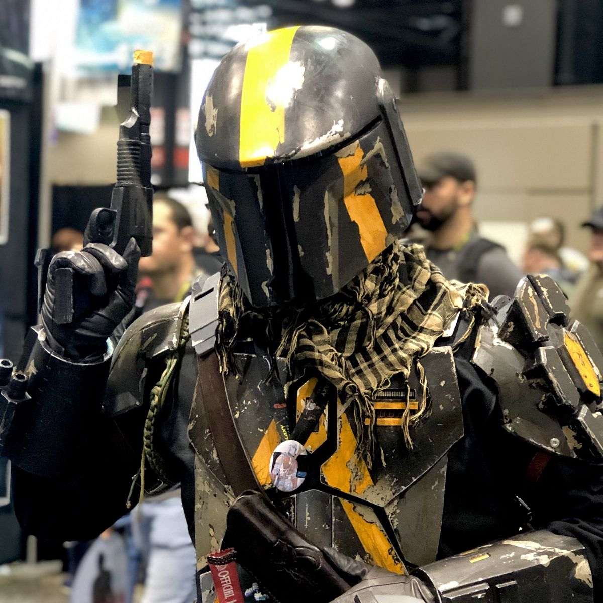 a yellow and black mandalorian armor cosplayer