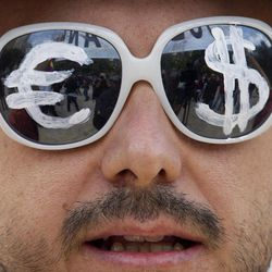 A protester wears glasses with the euro and dollar symbols painted on the lenses before a protest march in Madrid, Tuesday Sept. 25, 2012.  Thousands of people are expected to converge on the Spanish Parliament to protest the conservative government's handling of the economic crisis and to demand fresh elections. Organizers of the 'Occupy Congress' protest hope to form a protest chain around the building but heavy police reinforcements are likely to keep them well away.