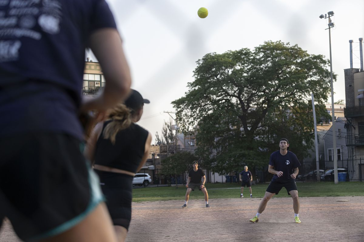 People play a game of softball at Wrightwood Park in Lincoln Park on Tuesday, July 27, 2021.