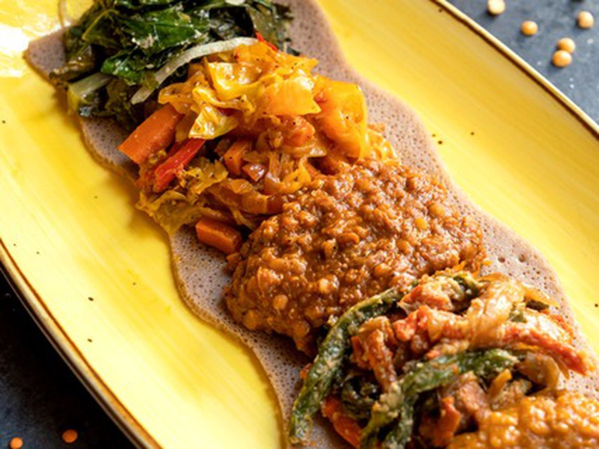 A yellow plate with multi-colored vegetables and lentils placed on it in a row