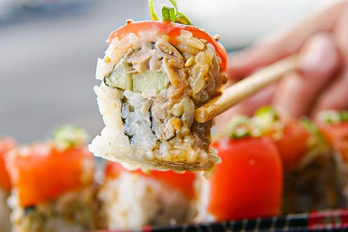 A vegan sushi roll held in a pair of chopsticks